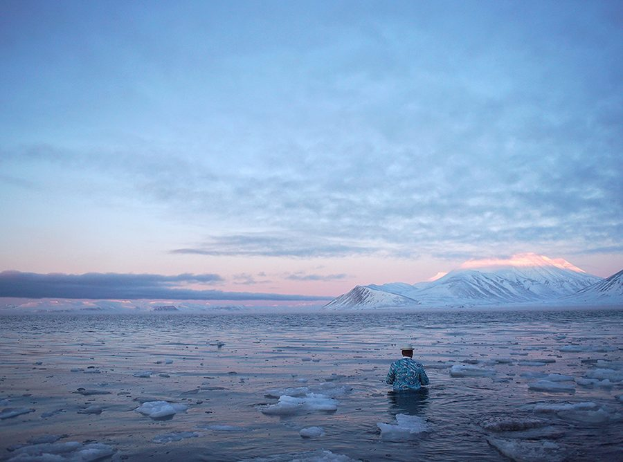 Artist wades into water, in Arctic Lanscape